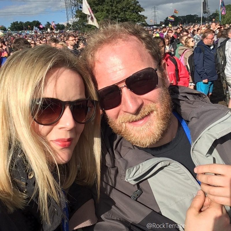 A blonde couple wearing sunglasses at Glastonbury festival