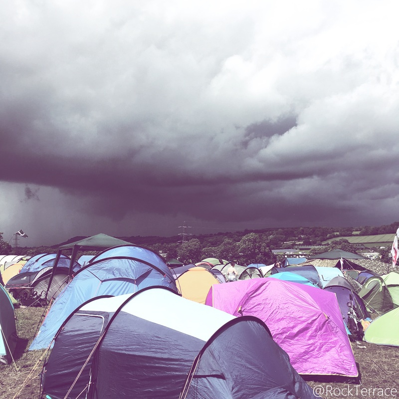 Colourful tents under a grey stormy sky at Glastonbury festival