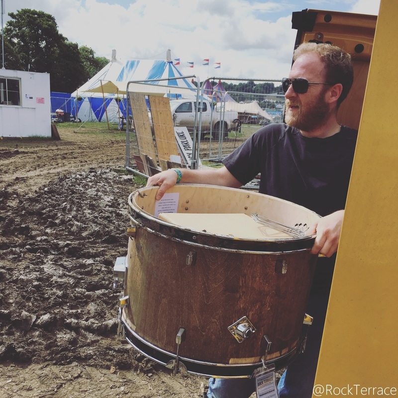 A bearded man wearing sunglasses unloading a wooden drum from a yellow van
