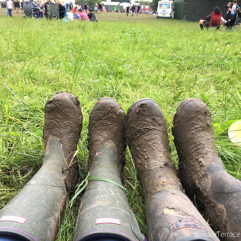 Two pairs of muddy wellies in a green field